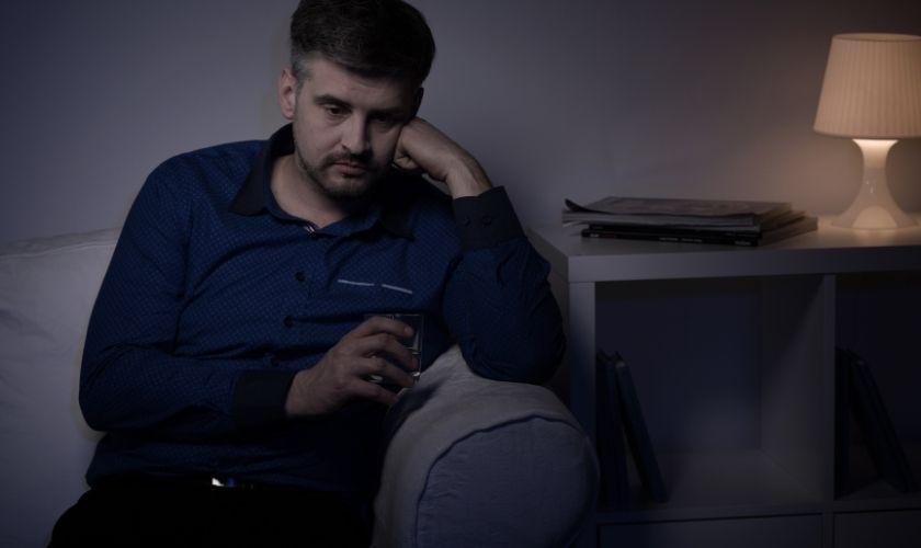 Adicciones en tiempos de Covid-19: hombre bebiendo alcohol en la soledad de su casa.