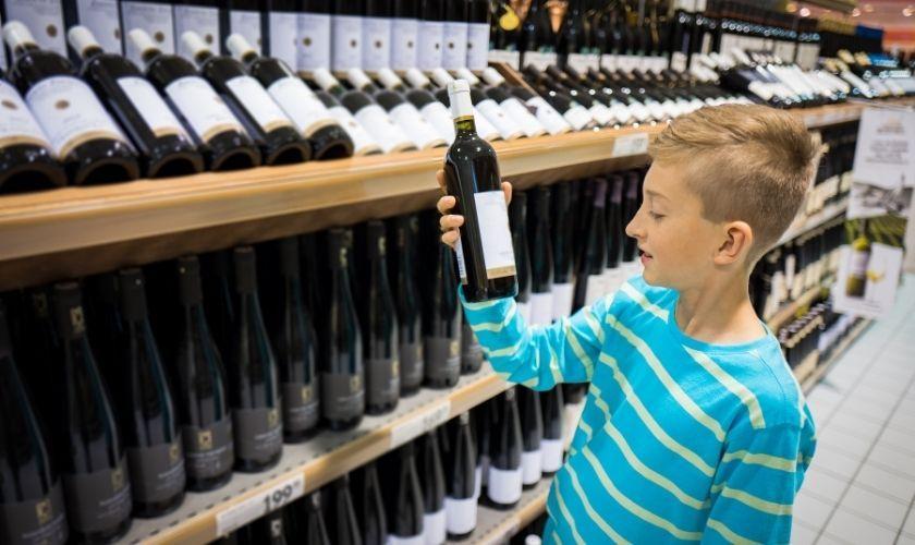 ¿Es el alcoholismo hereditario? | Niño mira etiqueta de botella de bebida alcohólica