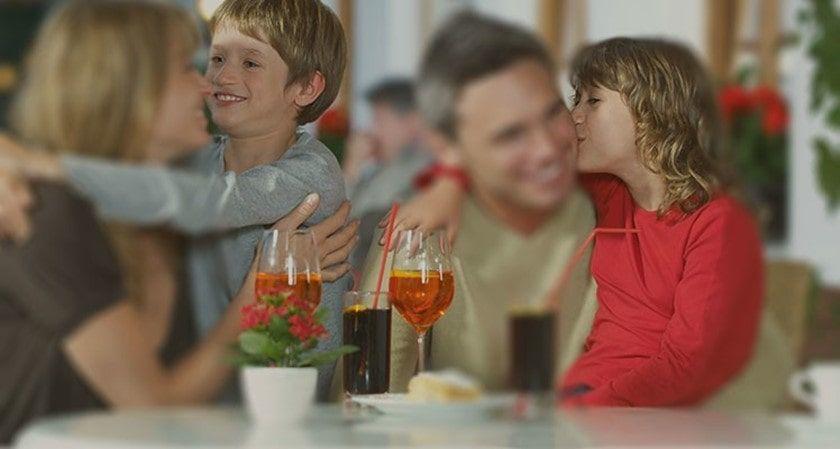 ¿Es el alcoholismo hereditario? Padres con sus hijos en un pub.