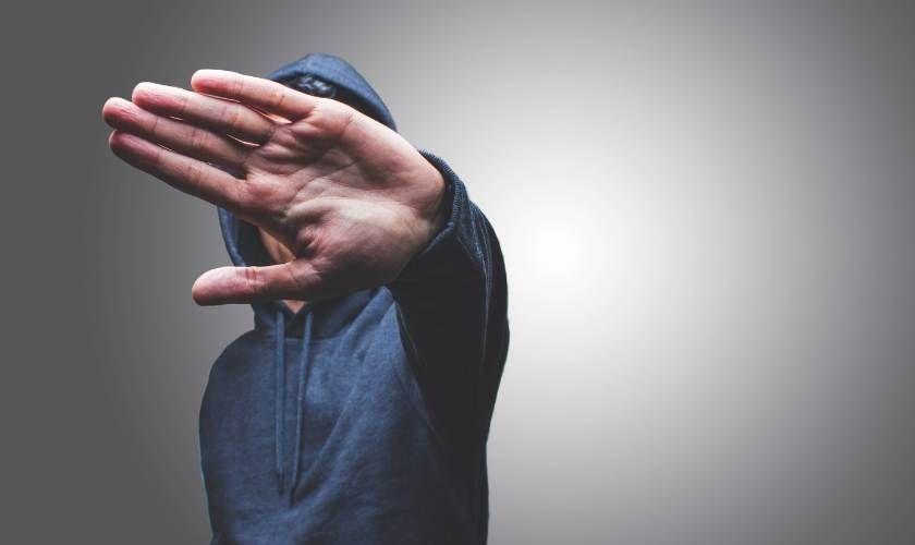 Negación de la adicción - Hombre ocultando su rostro con la mano.