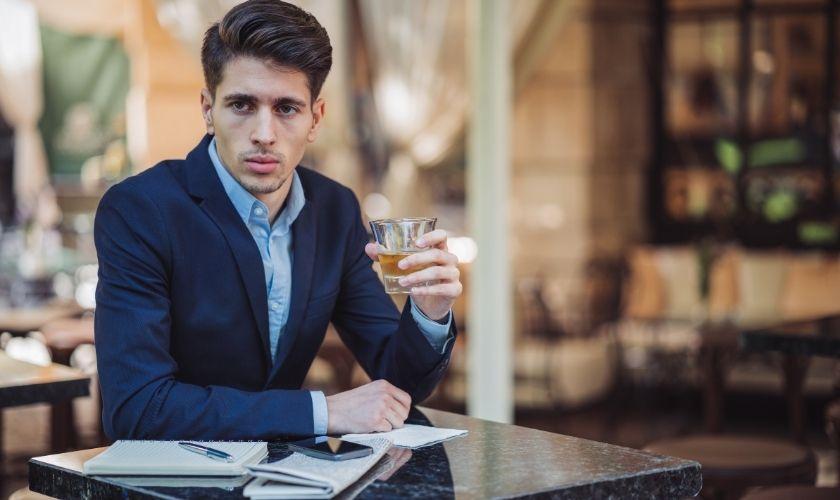 Riesgo de normalizar las adicciones - Hombre bebiendo en mesa