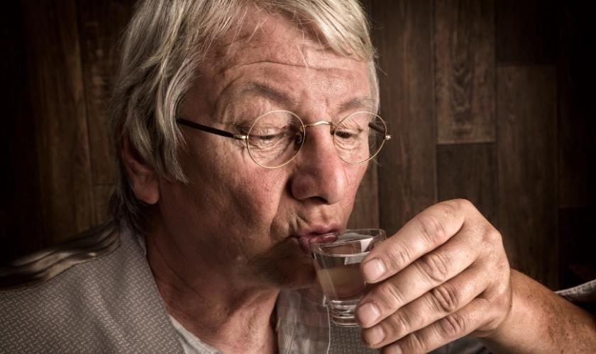 Adicción en las personas mayores | Hombre mayor bebiendo en vaso de chupito