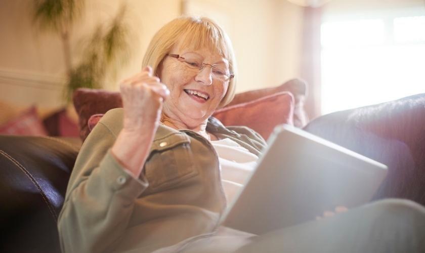 Adicción al juego online en personas mayores | Mujer jugando desde su tablet.