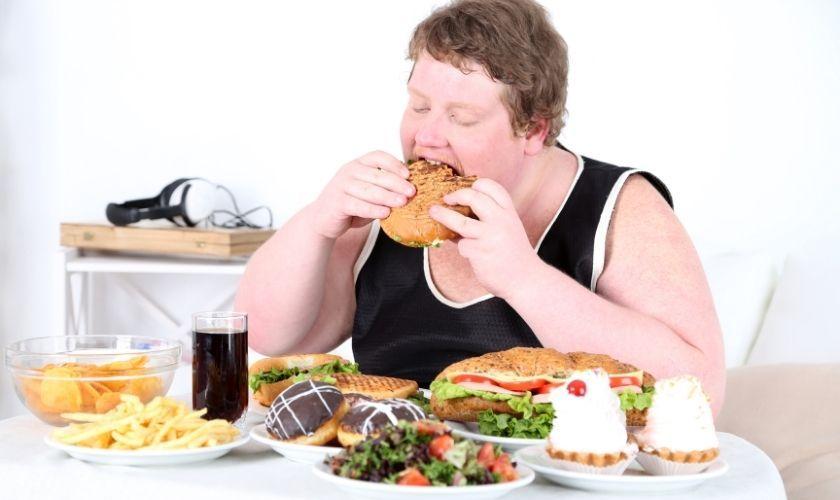 Comedor compulsivo - Joven comiendo gran cantidad de alimentos poco saludables