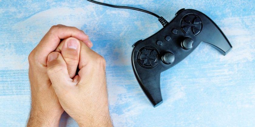 Aumenta el uso de videojuegos durante la pandemia: manos de gamer que intenta resistir para no jugar.